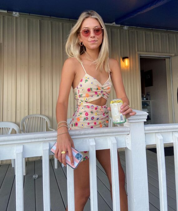 A girl standing on a front porch wearing sunglasses and holding her phone in one hand and a can in the other hand