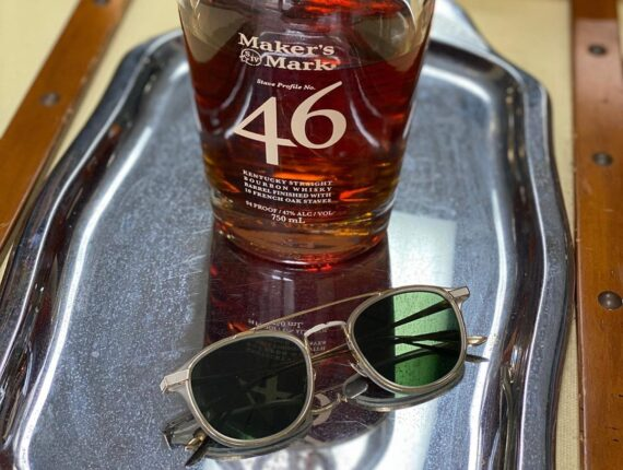 Sunglasses on Silver Tray with bottle of bourbon whisky.