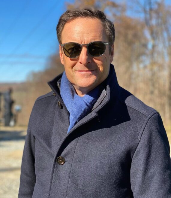 Chris Harrison smiling wearing green-tinted sunglasses with bright blue scarf and wool jacket.